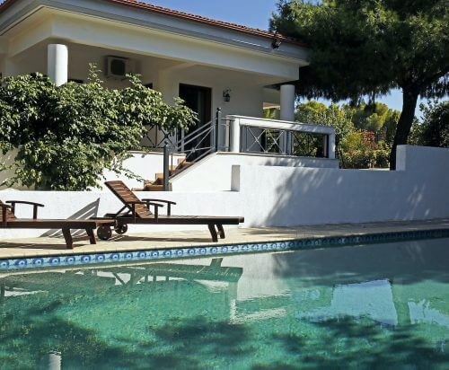 The Loutraki Green Villa swimming private pool with sun loungers is located under pine trees.